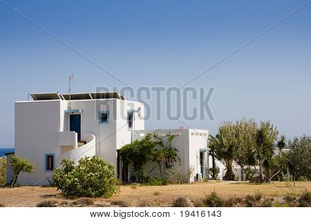 Small white and blue house over blue sky