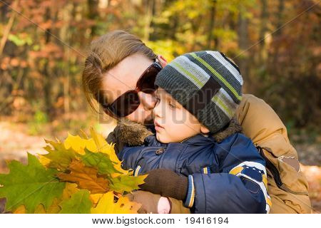 Mother and son whispering in autumn forest