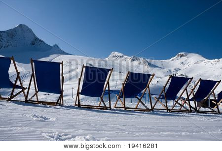 Deckchairs in front of ski slopes in alps