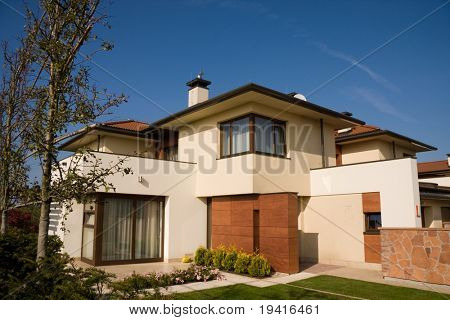 Single family yellow house over blue sky