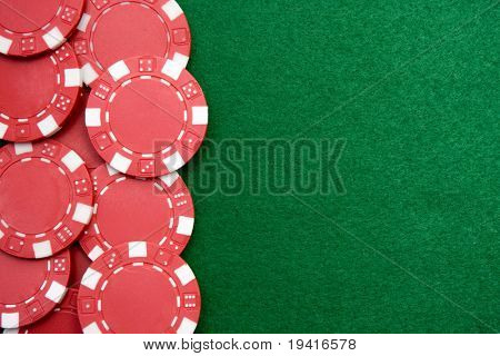 Red gambling chips on green felt background with copy space