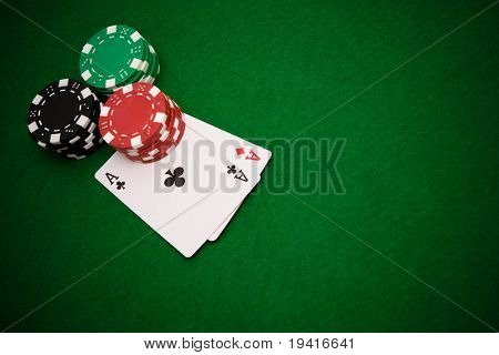 Two aces and stacks of gambling chips on green casino felt background with copy space