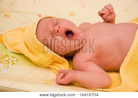 Newborn baby boy in yellow blanket yawning after bath