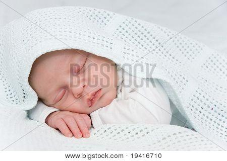 Newborn boy covered by blue blanket sleeping