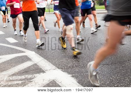 People running in marathon on a street in intentional motion blur