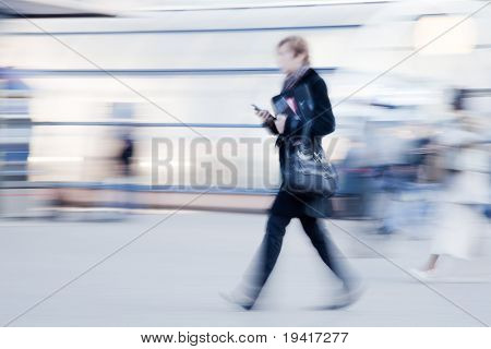 Intentionally motion blurred image of businesswoman with mobile phone in hand rushing to office in the morning