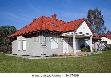 Single family house in grey color with green grass against blue sky