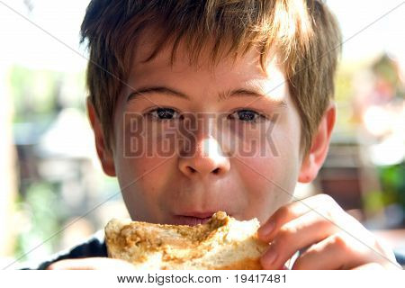 Joung Boy Is Eating Toast With Cream On Top, Enjoing Meal