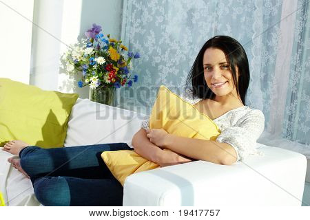 Portrait of brunette with pillow sitting on sofa and looking at camera