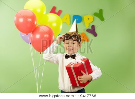 Porträt von glücklich Bursche mit Geschenkschachtel verschob lustige Brillen auf Geburtstagsparty