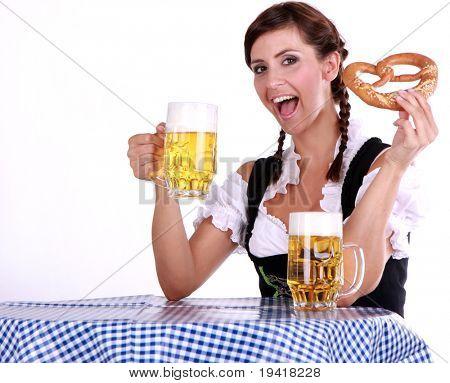Mujer morena bávara en tabla azul blanco con cerveza y bocadillos