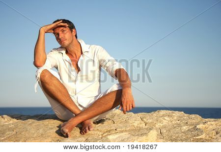 Man sitting on rock looking remote into the future