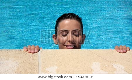Girl in the pool with hands and head outside the water