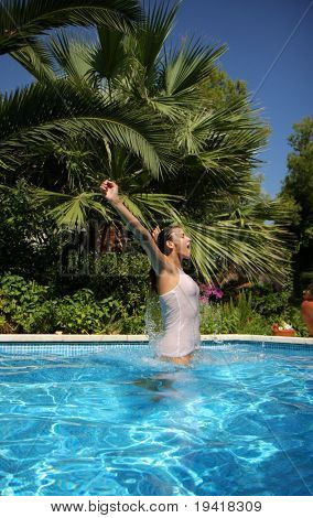 Woman jumping outside a pool with tropical palms in background