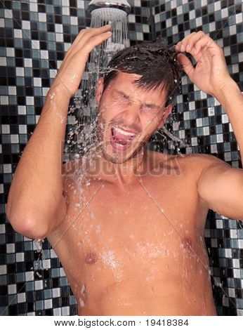 Man having shower in bathroom with soap and shampoo