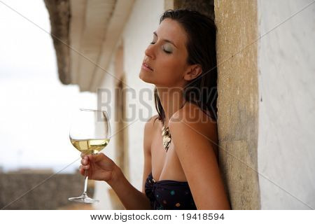 Female sitting on the roof of antic building with wine