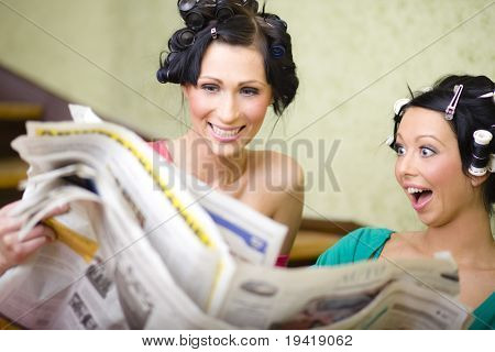 Two young housewives reading newspaper and looking for some cheap things