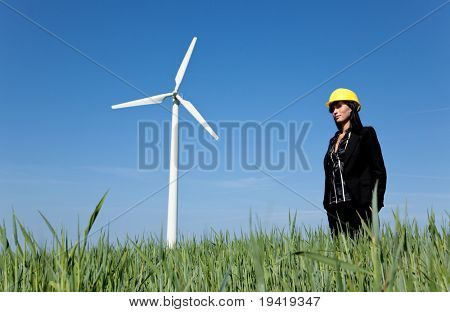 Renewable energy constructor standing on green field behind blue sky with windmill