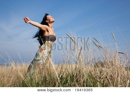 Carefree woman standing in field with blue sky