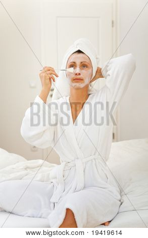 Pampered woman making anti-aging with face mask and care of the skin at home sitting in bathrobe on the bed