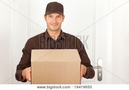 Freundliche Postbote mit einem Paket für Sie