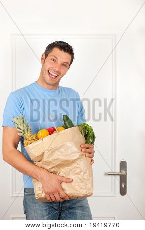 Smiling shopping man with bag filled with fruits, food, vegetables from supermarket coming home staying on apartment door