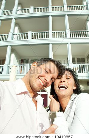 Key holding smiling hapy couple in front of new real estate balcony residential house
