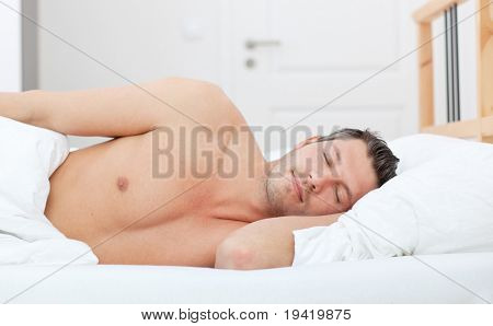 Cheerful man lying in bed and having sweet dreams while sleeping
