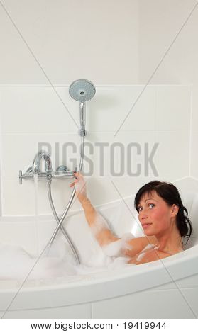 Woman at home taking a bath with a lot of foam in tub and shower