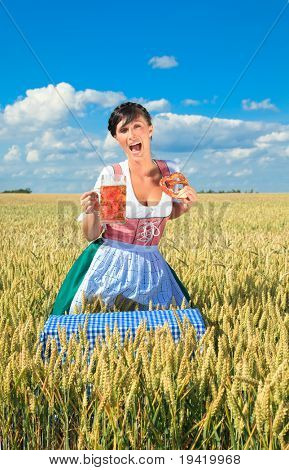 oktoberfest female waitress standing in cornfield meadow holding beer wearing traditional dirndl