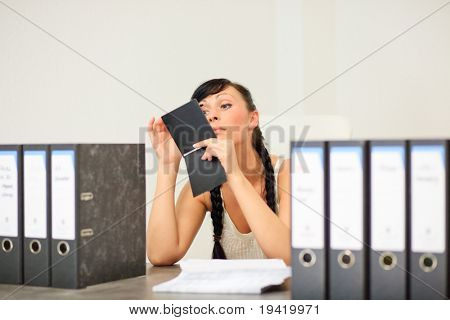 business woman in office putting on her make up feeling bored