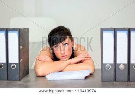 Jobless business woman on desk in office dreaming and posing upset loosing job