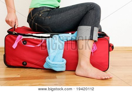 Sitting on overweight and overfilled baggage trying to close luggage while packing the bag