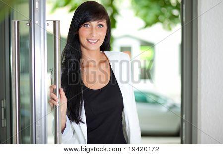 Door opening business student woman coming in to begin new career