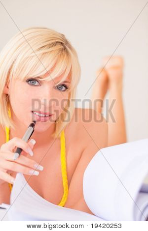 Learning blond student girl making college university homework at home holding pen and lying down on couch