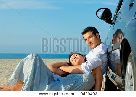 Beach sea coastline lying together masculine and feminine pair of to young adults driver loving embracing and the togetherness being in love