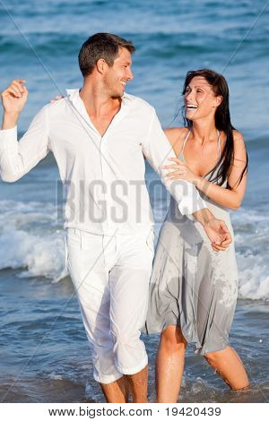 Blue Waves running laughing handw holding sea water lover couple enjoying summertime in ocean holding together watersport splash wet