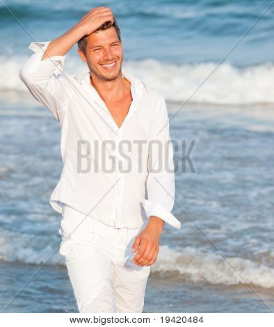 Portrait of cute happy smiling male walking carefree on the sunny coast thinking positive