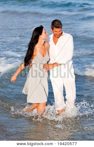 Lovely attractive cuddling pair of boyfriend and girlfriend laughing while walking healthy in ocean sea water
