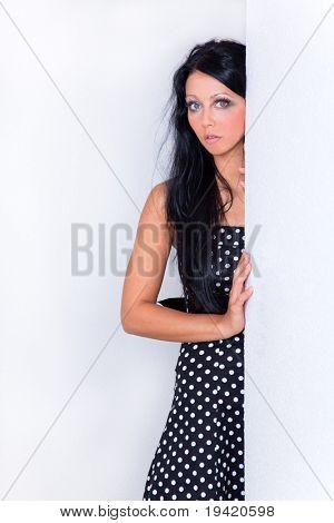 Neugierig Seite suchen weibliche Fotomodell auf weiße Wand im Einkaufszentrum in Umkleidekabine anzeigen