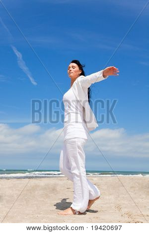 Arms outstretched standing walking woman on coast feeling free