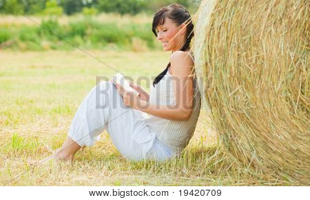 Relaxing nature girl sitting in golden field reading book feeling carefree