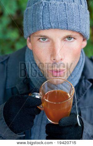 Caída de hombre calentando con té caliente en tiempo de frío otoño invierno sentado en un banco en un verde parque
