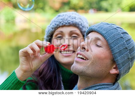 Funny playful autumn fall couple making soapbubbles