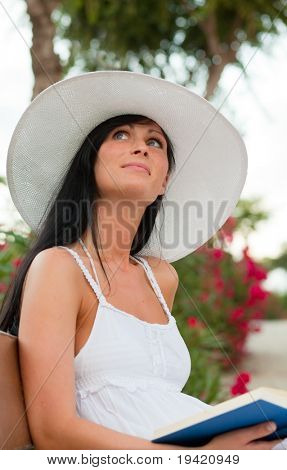 Book reading thinking smiling summertime woman in tropical garden