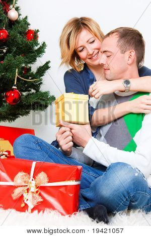 Happy smiling embracing lovely couple celebrating christmas eve with present gifts