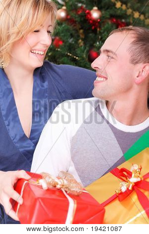 Happy smiling embracing lovely couple celebrating christmas eve with surprise present gifts
