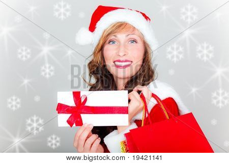 Santa woman with christmas wishing list and a lot of shopping bags smiling wearing red cap and santa clothes