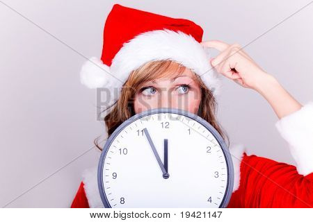 Woman thinking about forgotten xmas gifts holding clock