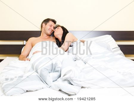 Scenic in bedroom of pair of loving young couple lying in bed looking eachother romantic while cuddling and embracing
